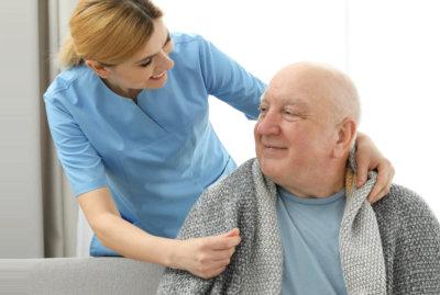 caregiver giving blanket to a senior man